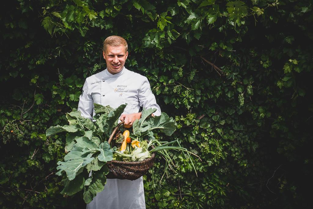 Der Koch Daniel Reuner hält einen großen Korb mit Gemüse aus dem Garten