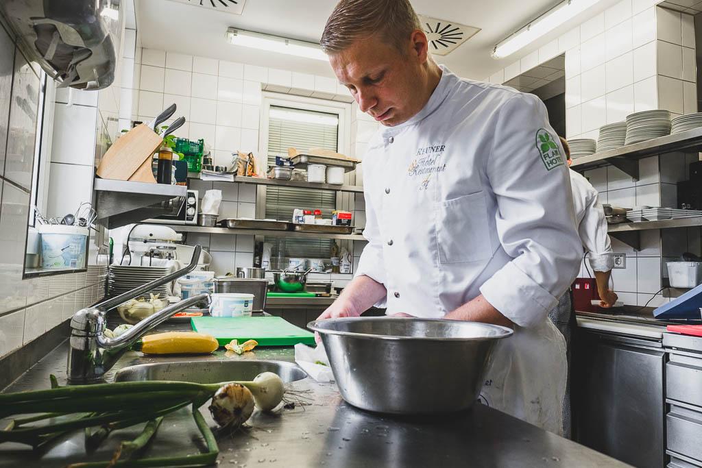 Daniel Reuner bereitet Schüttelzucchini und Schüttelkohlrabi mit frischem Salat aus dem Garten in der Küche des Flair Hotel Reuner zu
